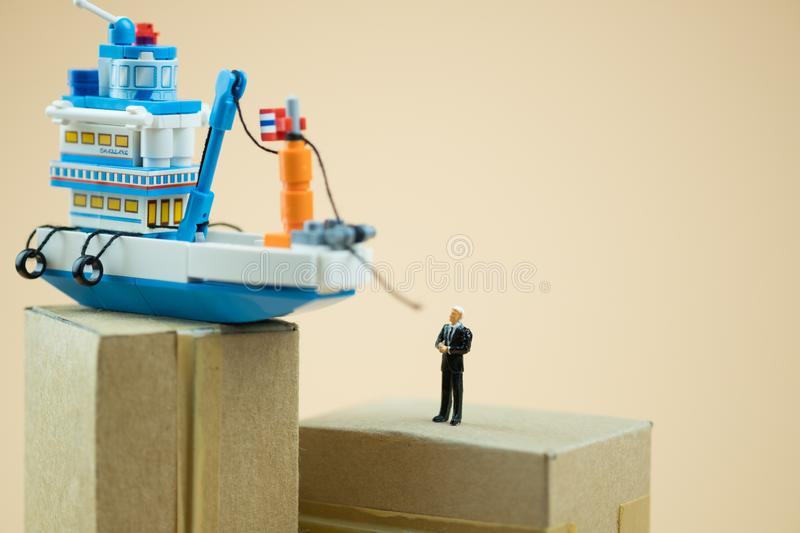 Miniature people businessman with boat. Concept of ship cargo delivery stock photography
