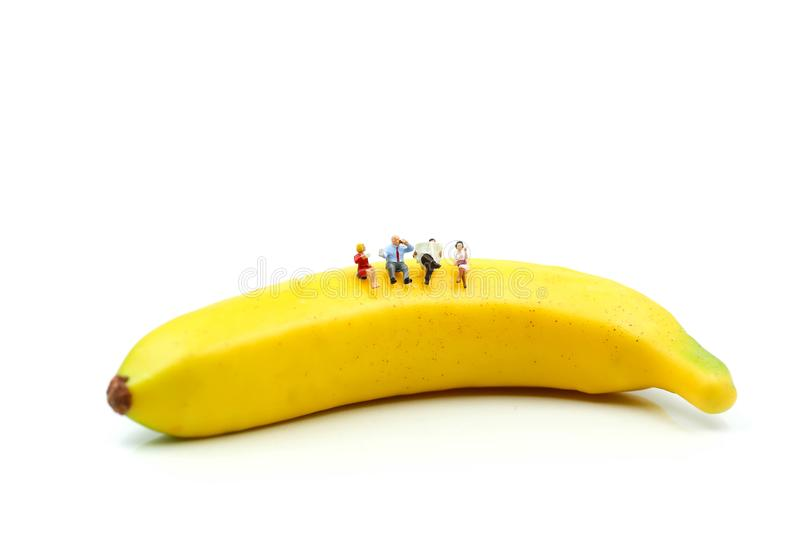Miniature people : Businessman and friend sitting on banana,relax and good health concept. royalty free stock image