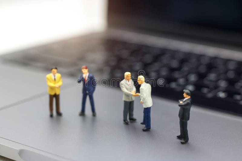 Miniature people: Businessman handshake to business success Online on laptop. Commitment, agreement, investment and partnership c. Oncept stock photo