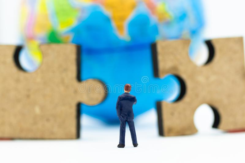 Miniature people : Businessman look at jigsaw pieces and have world map for background. Image use for solve, solution stock photo