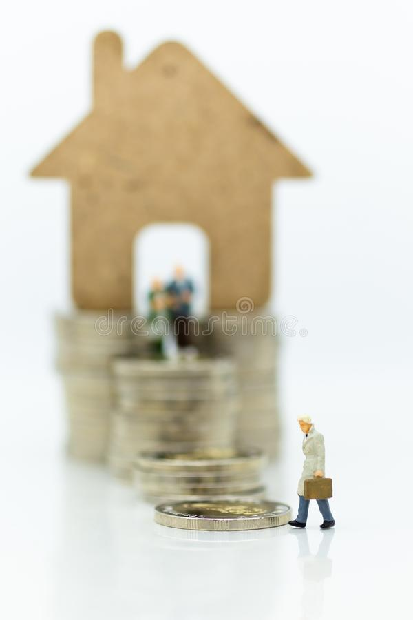 Miniature people: Businessman looking for housing for the future. Image use for home for family.  royalty free stock photo
