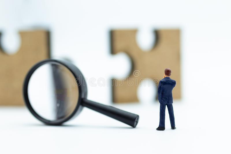 Miniature people : Businessman looking at jigsaw pieces through a magnifying glass. Image use for solve, solution, business. Concept stock image