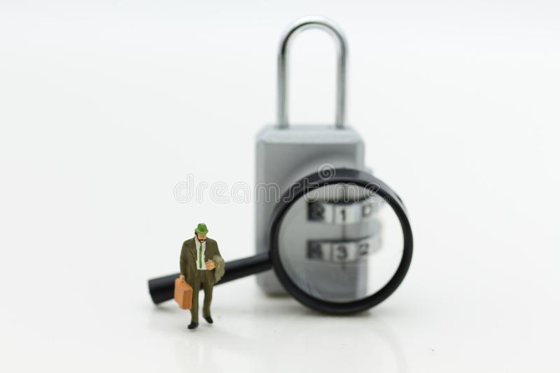 Miniature people: Businessman with a magnifying glass and master key encoding. Image use for background security system royalty free stock images