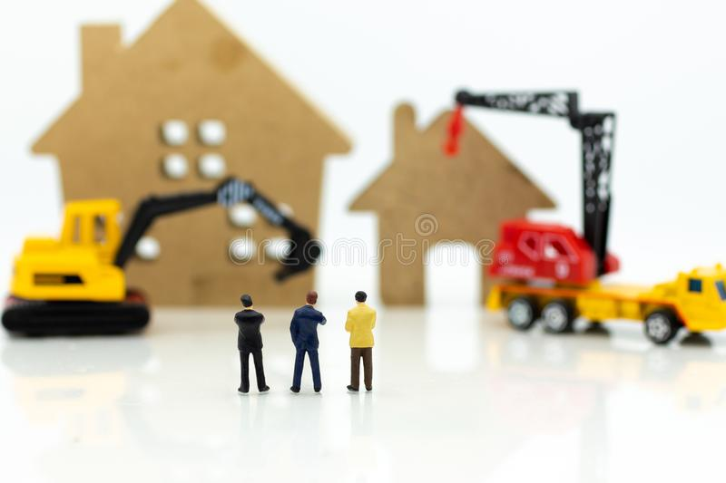 Miniature people: Businessman meeting for building home . Image use for construction, business concept.  royalty free stock images