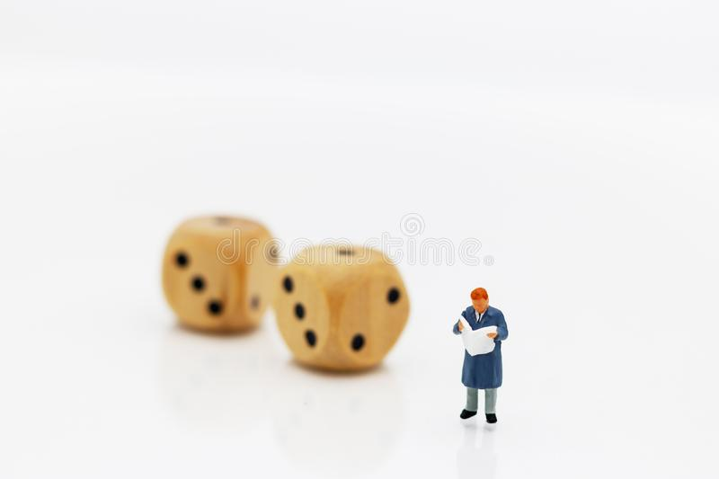 Miniature people: Businessman reading book with dice. Eduation and business Concept royalty free stock photos