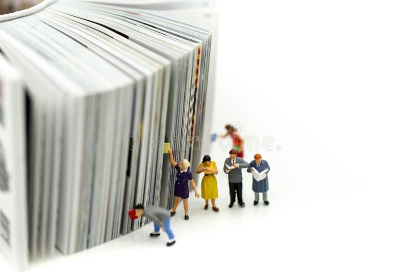 Miniature people: Businessman reading newspaper and sitting on b stock image