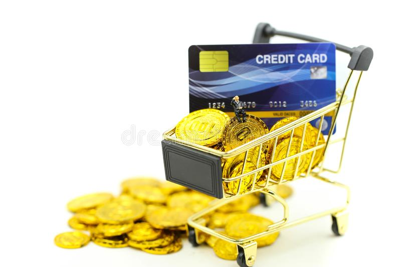 Miniature people : Businessman with Shopping cart,Credit cards and money stacks of coins shopping online business concept stock photos