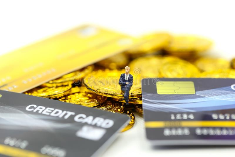 Miniature people : Businessman with Shopping cart,Credit cards and money stacks of coins shopping online business concept stock image