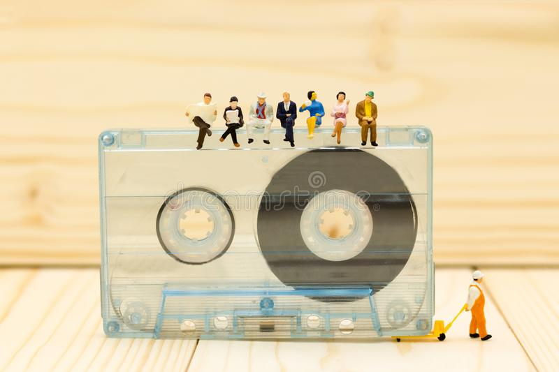 Miniature people: Businessman sit and reading newspaper on Compact Cassette. Image use for music , business concept.  royalty free stock images