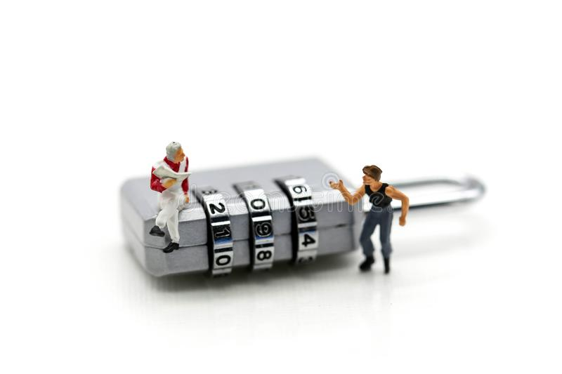 Miniature people : businessman sitting on metal security lock key with thief. stock photo
