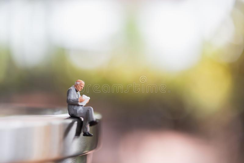 Miniature people: Businessman sitting  reading book outdoor stock photos