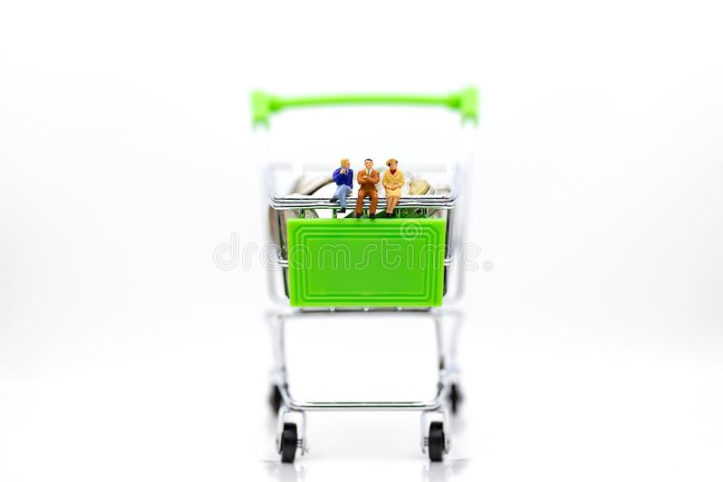 Miniature people : Businessman sitting on shopping cart on stack of coin. Image use for retail business concept.  royalty free stock photography