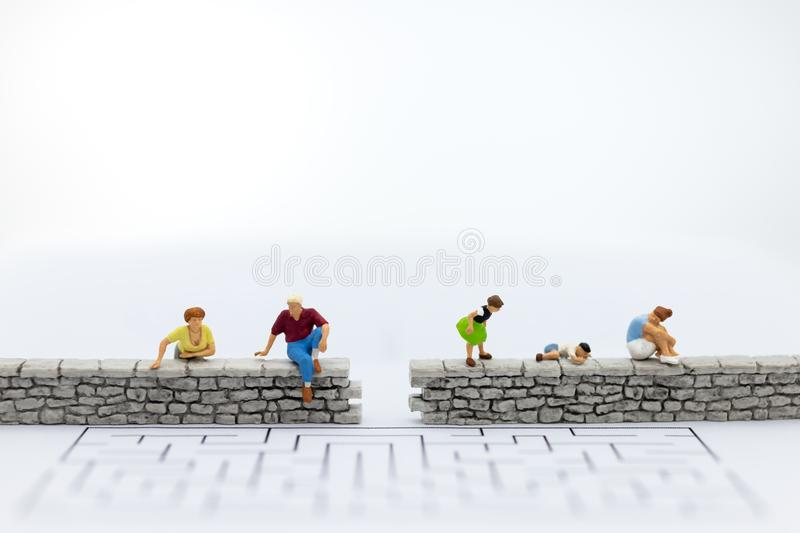 Miniature people : Businessman sitting on the wall . Image use for business , spend time for family.  royalty free stock photo
