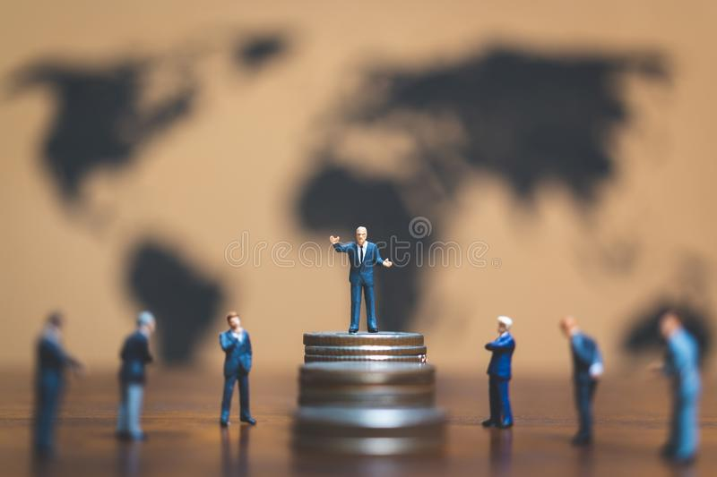 Miniature people: Businessman on stack of coin, money and financial business success concept. stock photos