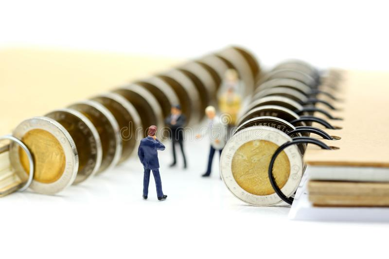 Miniature people : Businessman stand with coins of book,education or business concept. royalty free stock photos