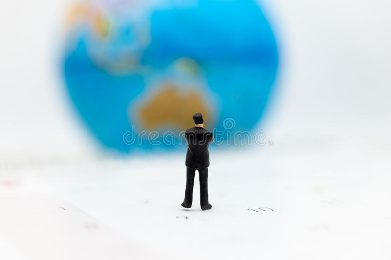 Miniature people : Businessman standing on the calendar to set the date for the international meeting . Image use for business. Meetings concept stock photography