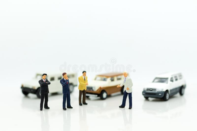 Miniature people : Businessman standing with car. Image use for Advertising product in the market today. Competition on the business trading stock photo