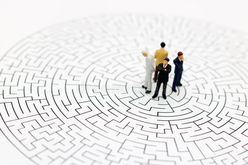 Miniature people: Businessman standing on center of maze. Concepts of finding a solution, problem solving and challenge. royalty free stock image