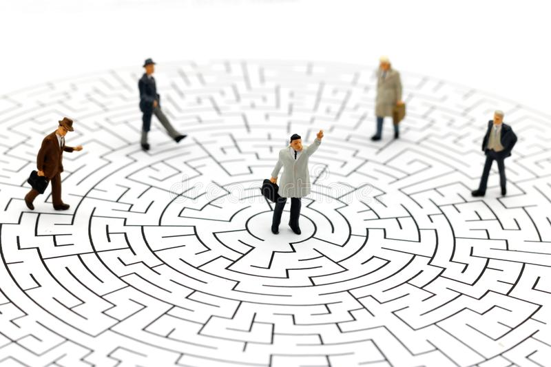 Miniature people: Businessman standing on center of maze. stock photo