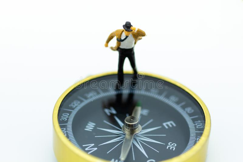 Miniature people: Businessman standing on compass. Image use for direction of business royalty free stock photography