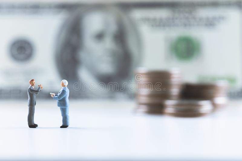 Miniature people, Businessman standing on dollar bill with coin stack step up background stock photo