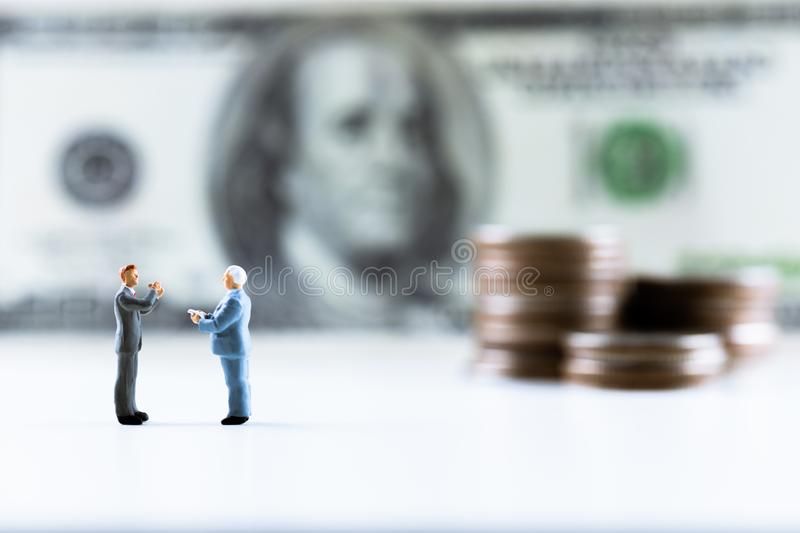 Miniature people, Businessman standing on dollar bill with coin stack step up background royalty free stock photography