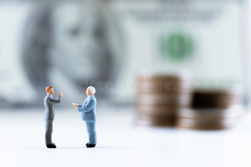 Miniature people, Businessman standing on dollar bill with coin stack step up background royalty free stock photo
