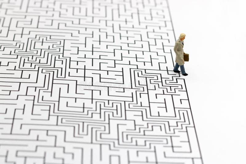 Miniature people: Businessman standing on finish of maze. Concepts of finding a solution, problem solving and challenge. royalty free stock photography