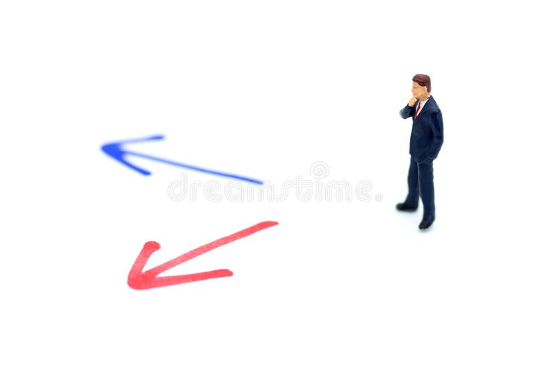 Miniature people: Businessman standing in front of arrow pathway choice. Image use for business decision concept, new the way royalty free stock photo