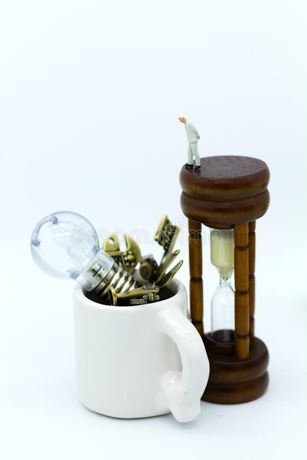 Miniature people: Businessman standing on hourglass and looking to equipments in the cup. Image use for equipment, tools royalty free stock images