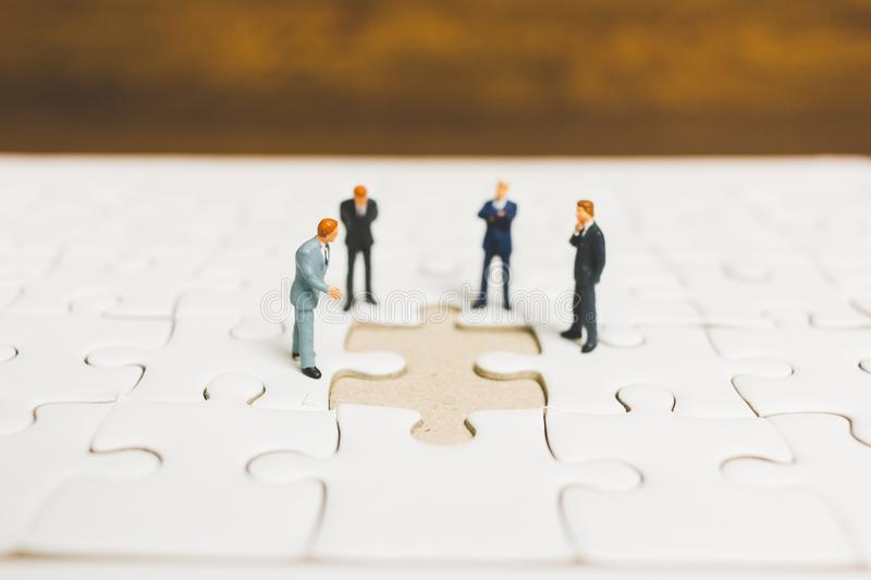 Miniature people: Businessman standing on jigsaw royalty free stock image