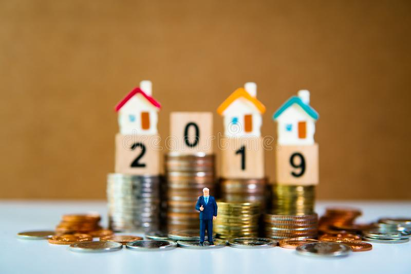 Miniature people, businessman standing with mini house, wooden block 2019 and pile of coins background using as financial, job royalty free stock photo