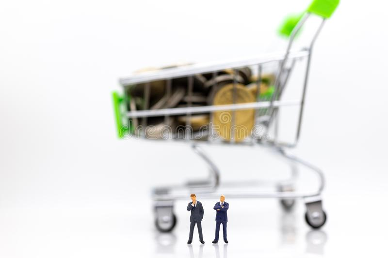 Miniature people : Businessman standing with shopping cart on stack of coin. Image use for retail business concept royalty free stock photos