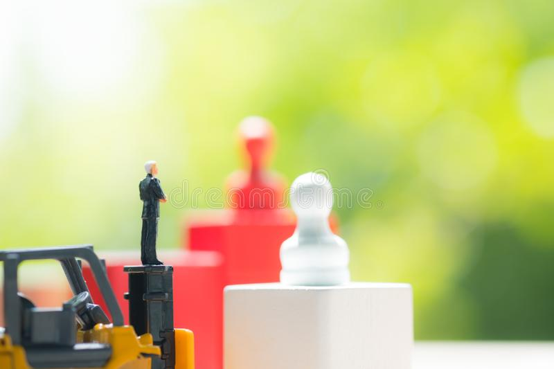 Miniature people businessman standing on toy yellow forklift stock photography