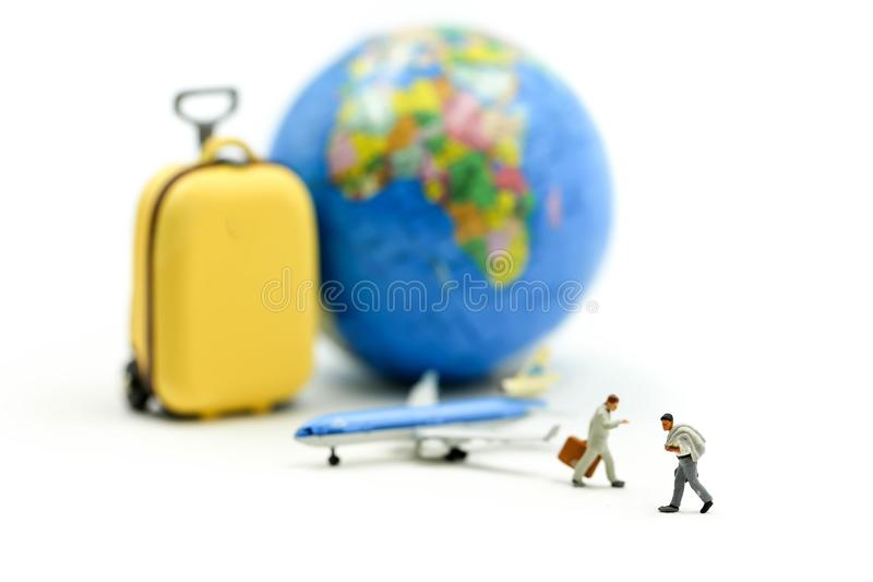 Miniature people : Businessman walking with Suitcase,mini worldmap, and airplane,travel concept stock photography