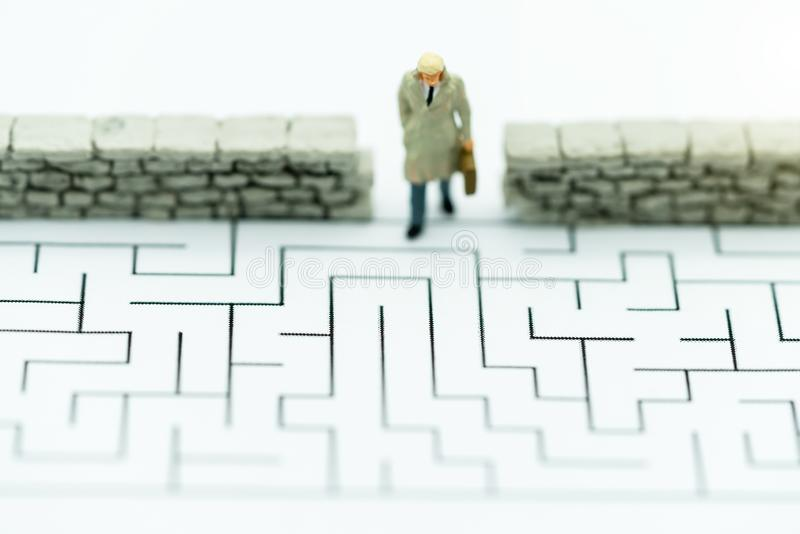 Miniature people: Businessman walking to wall in maze. Concepts of finding a solution, problem solving and challenge stock photo