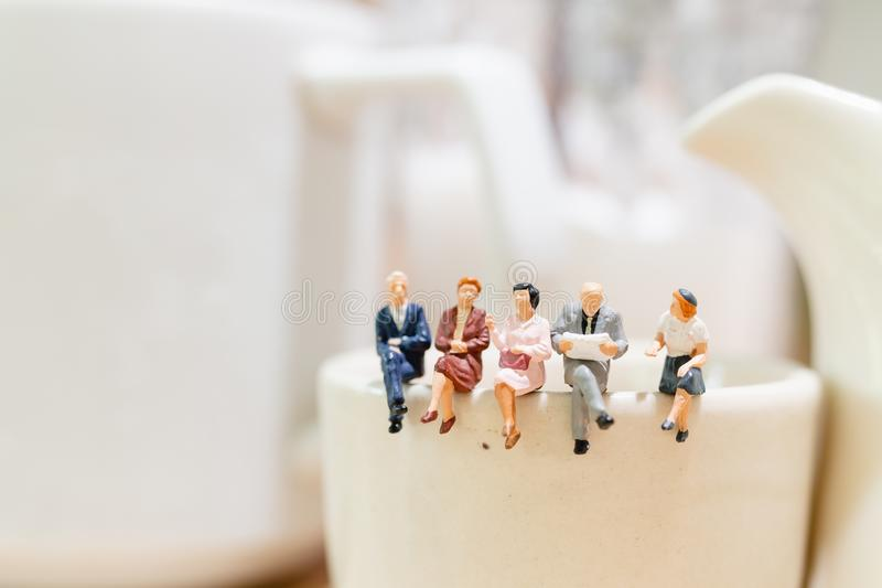 Miniature people : businessman and woman sitting on a cup of tea stock photo