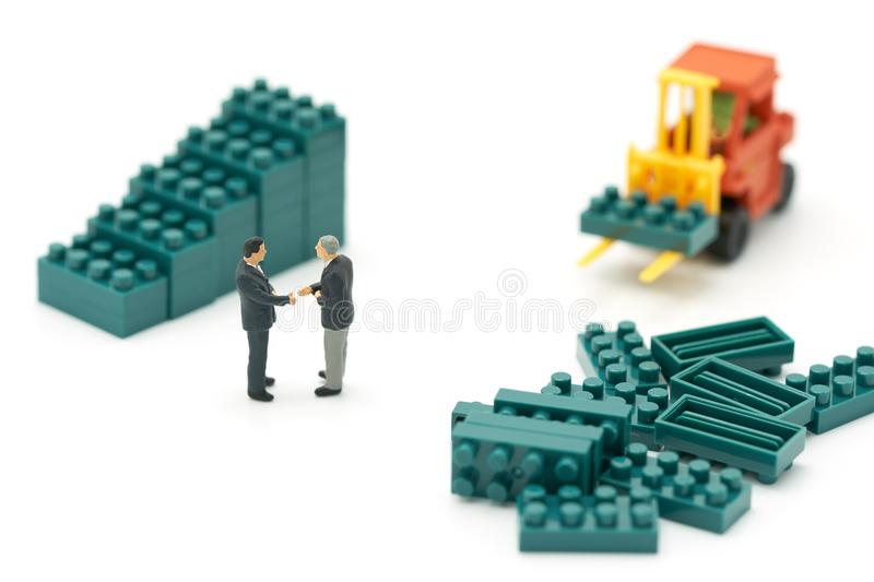 Miniature 2 people businessmen Shake hands with High-lifted forklift trucks are a great way to grow your business as a high-tech, royalty free stock image