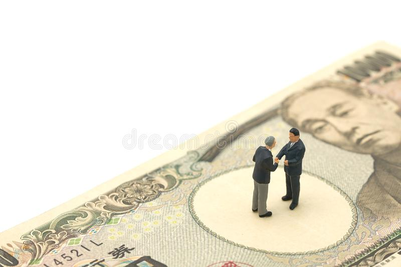 Miniature 2 people businessmen Shake hands Stand on Japanese banknotes worth 10, 000 yen using as background business concept and. Finance concept with copy stock image