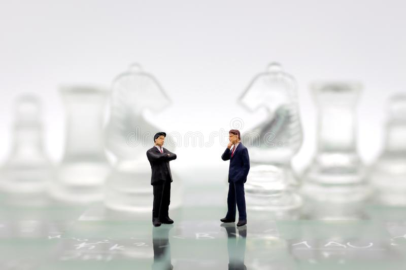 Miniature people, Businessmen stand on opposite sides of the chess game, separate party , benefit, use as a business competition. Concept stock image