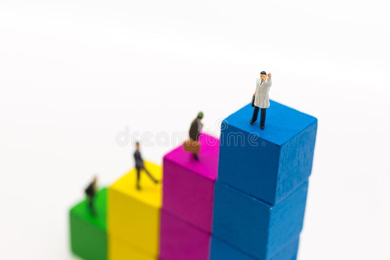 Miniature people : Businessmen stand on top of graphs, showing increased profits from doing business. Using as business concept stock images
