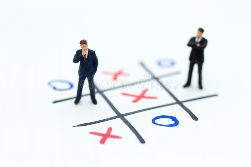 Miniature people: Businessmen stand on XO game board. Image use for business competition concept.  stock photos