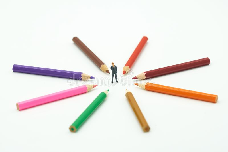 Miniature people businessmen standing Colorful wooden pencils surround a circle on a white background. Make a center Can be used stock photo