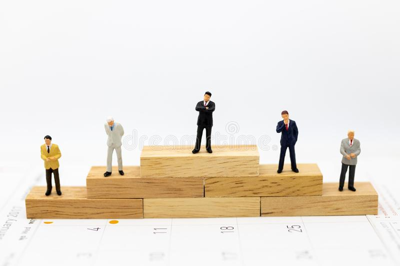 Miniature people : Businessmen standing in various positions of wooden , indicating the sequence of work, used as a business. Concept stock photography