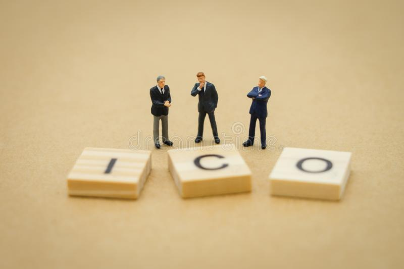 Miniature people businessmen standing with wood word ICO Initial Coin Offering using as background business concept and finance. Concept with copy space for stock photos