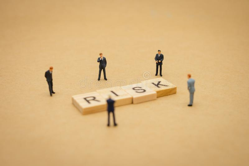 Miniature people businessmen standing with wood word RISK using as background business concept and Risk concept with copy space royalty free stock photography