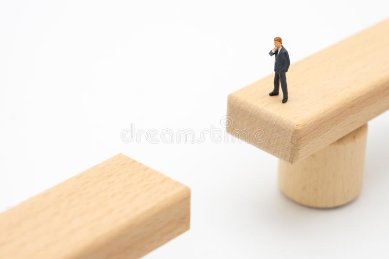 Miniature people businessmen Standing on a wooden bridge Looking at the opposite side, analyzing the way to reach the destination stock photography