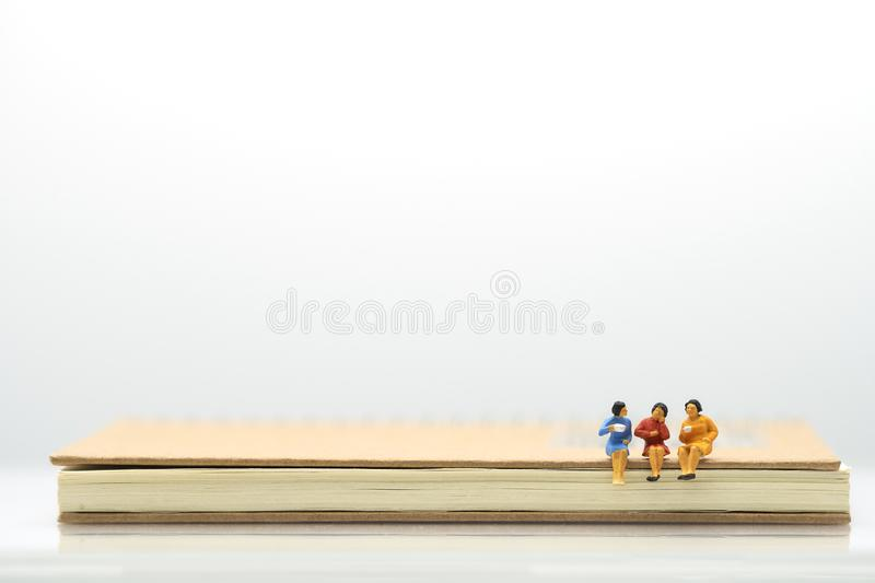 Miniature people Businessmen talk, sip coffee. sitting on notebook using as background business concept with copy space. For your text or design stock photography