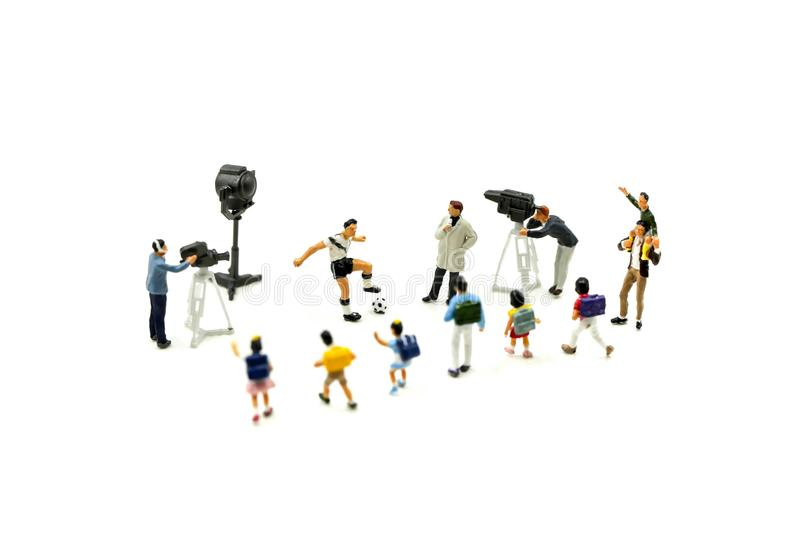 Miniature people : Cameramen, photographers and reporters interviewing football player with children,student. stock images