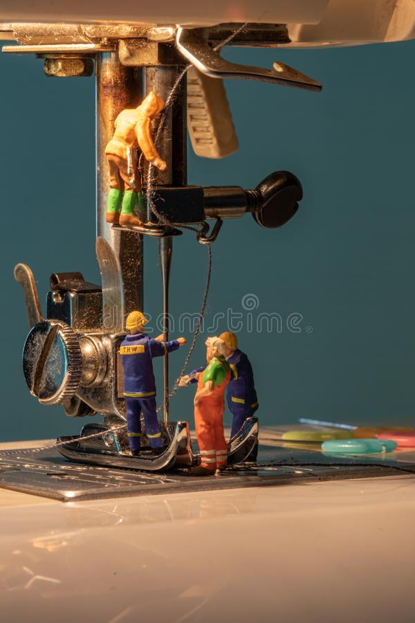 Miniature people change thread on sewing machine stock photography